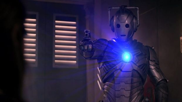 A newly activated Cyberman holds Clara in its sights.