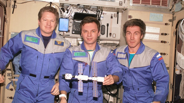 Expedition 1, the first space station crew, poses inside the Zvezda service module with a model of the young International Space Station. Pictured in December 2000 (from left) are Commander William Shepherd and Flight Engineers Yuri Gidzenko and Sergei Krikalev. - Via NASA